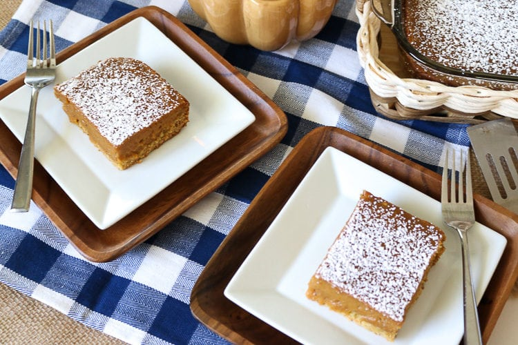 Two square plates with cut pieces of pumpkin gooey butter cake with powdered sugar topping
