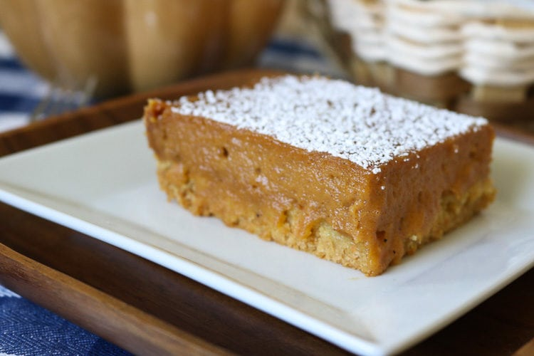 A square slice of Pumpkin Gooey Butter Cake with powered sugar.