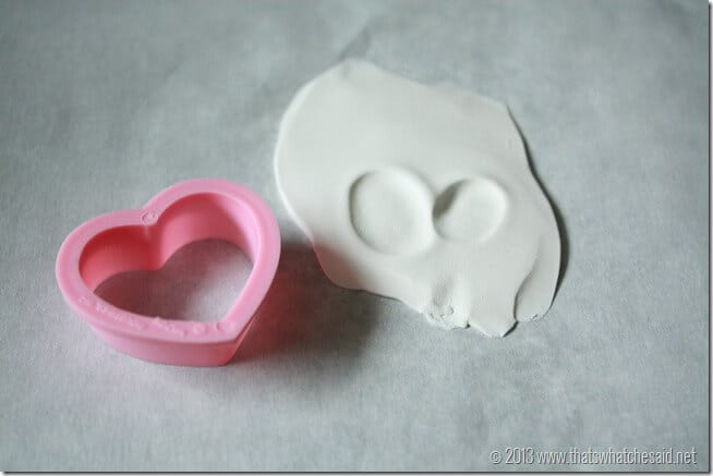 Small heart cookie cutter next to pressed clay with thumbprint v
