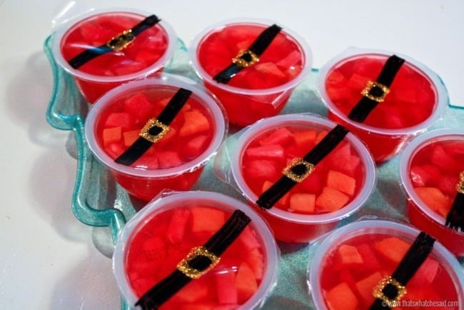 Red gelatin fruit cups with a santa belt drawn on the top to create Santa Fruit Cups