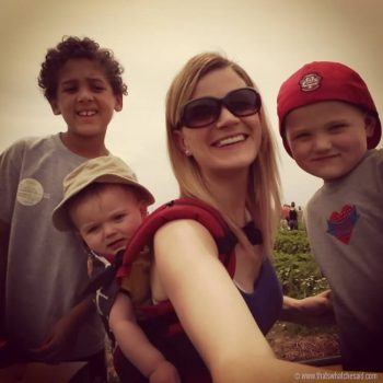 Mom with three boys selfie picture while strawberry picking