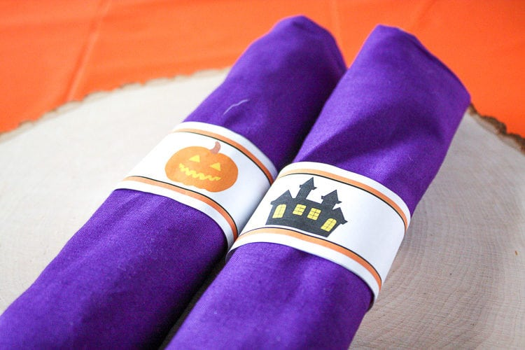 Purple rolled fabric napkins with halloween water bottle labels as napkin rings