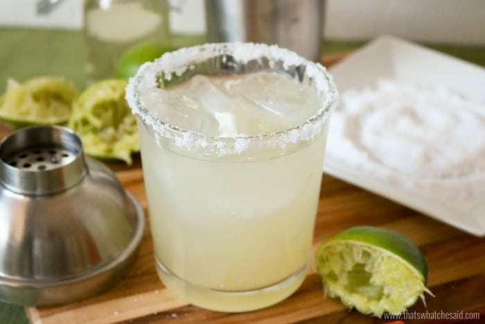 Classic Margarita in a rocks glass with salt rim.  Shaker and salt ingredients in the background.