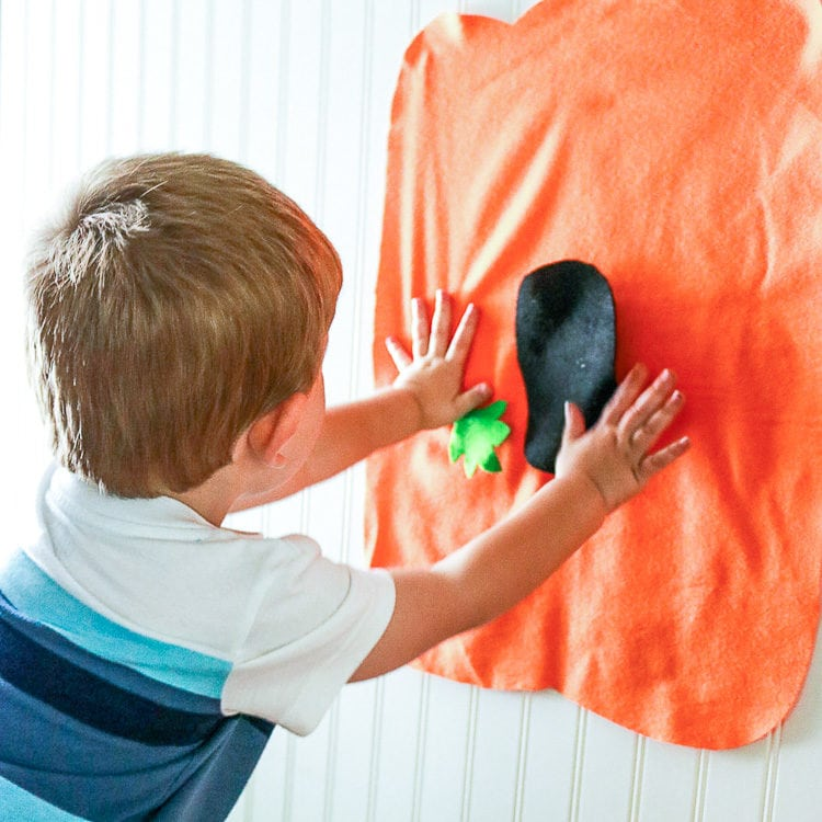 Child adding felt face pieces to a big felt pumpkin shape
