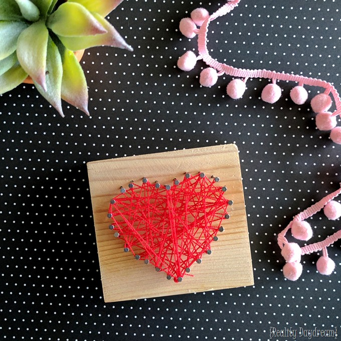 Small block of wood with nails and red string in a heart shape