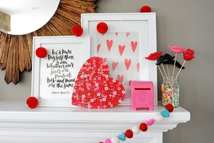 Valentine Mantel with wooden heart that is covered in red and pink buttons for mantel decor
