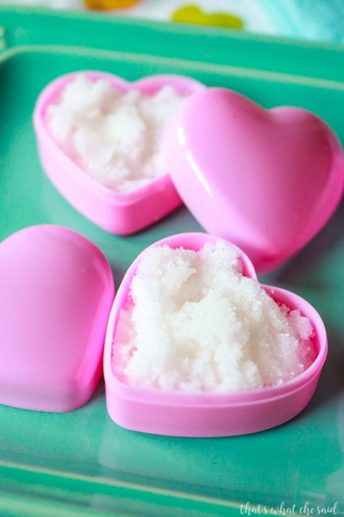 DIY Homemade Lip Scrub made with Sugar and coconut oil in heart containers on aqua plate