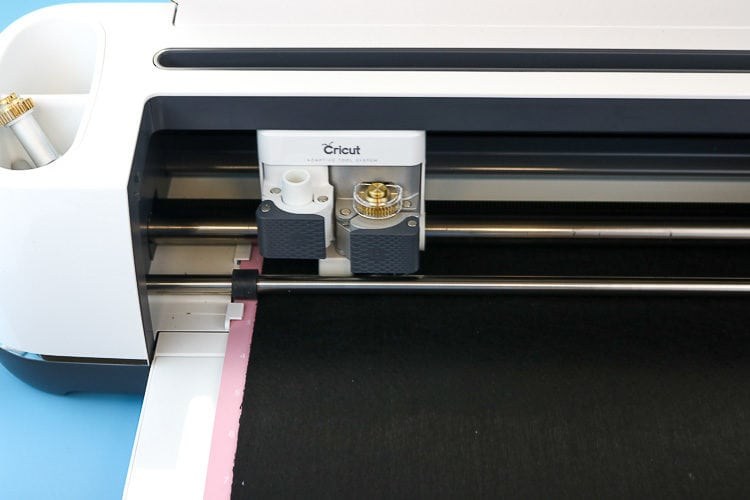 Cricut Maker with Pink mat inserted with black felt on it