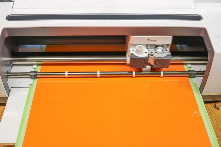 Cricut Maker with Orange Window Cling loaded on a Standard Green Mat