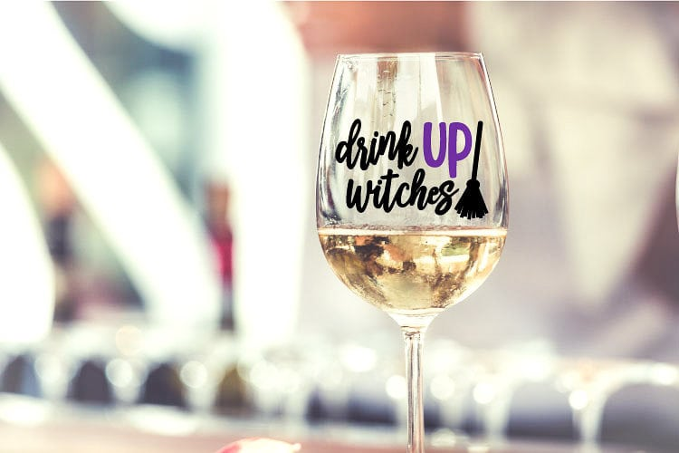 "Wine GLass with Vinyl decal that reads ""Drink Up Witches"" and a broomstick"
