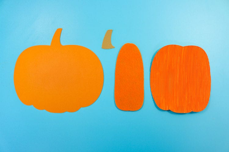 4 parts of the pumpkin each cut in a different material. Cardstock, corrugated cardboard and felt.