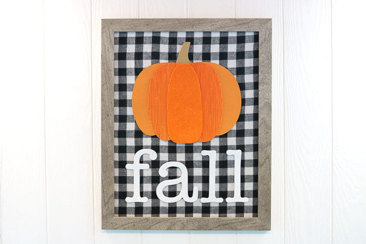 Framed sign with buffalo plaid fabric, a mixed media pumpkin and the word fall in chipboard