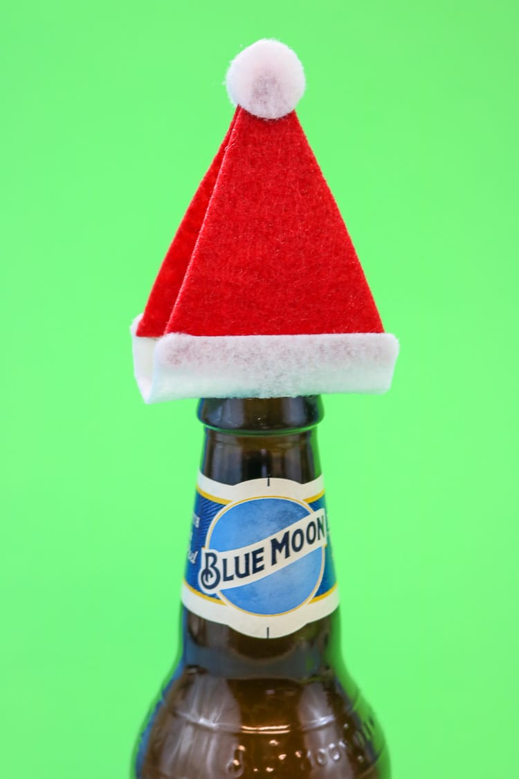"Add the Santa Hats to Tops of Bottles to create a fun ""gift wrap"" idea for a 6 pack"