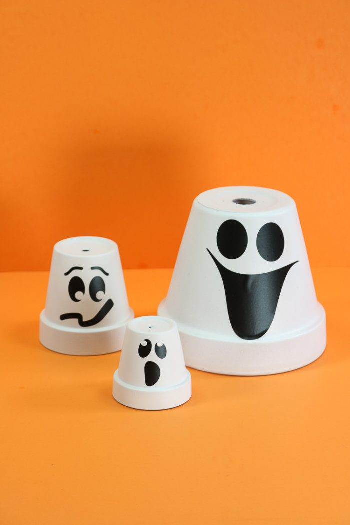 Three terracotta clay pots overturned, painted white and ghost faces added for Halloween decor ideas.
