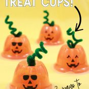 four fruit cups turned upside down and a pipe cleaner stem has been added with jack o lantern face to create pumpkin treat cups