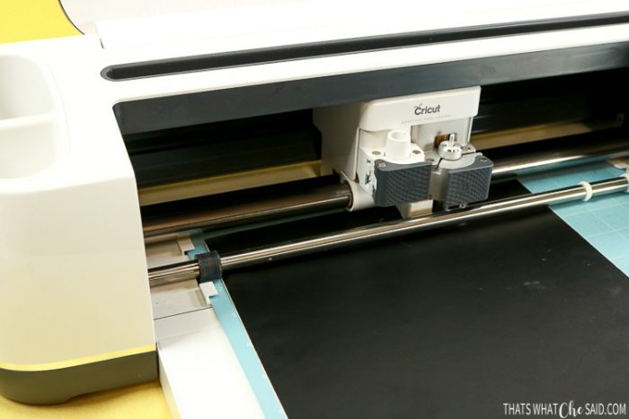 Cricut Maker cutting black craft vinyl into jack-o-lantern faces
