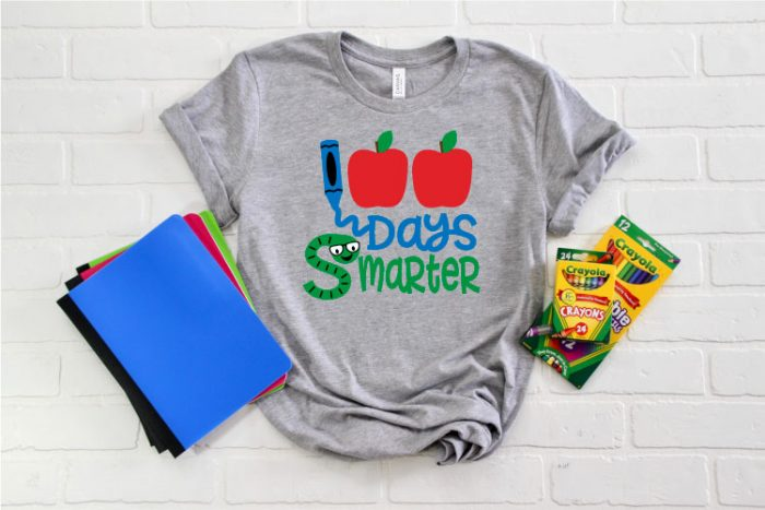 Grey T-shirt with some school supplies staged around it and the 100 Days smarter SVG file cut and applied in iron on.