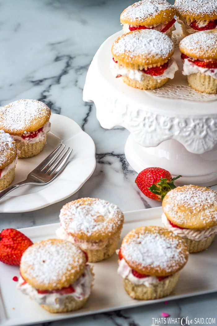 Finished strawberry shortcake cupcakes on a rectangle platter, small plate and cake plate ready for brunch