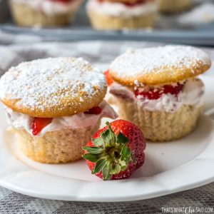 Plate with 2 White cupcakes with tops cut off, strawberry cream added and tops returned with a powdered sugar dusting.