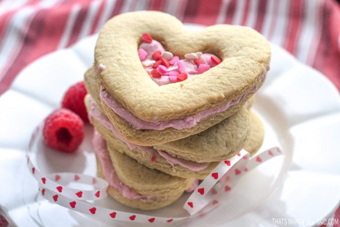 Shortbread heart cookies sandwiched with raspberry filling stacked on a plate