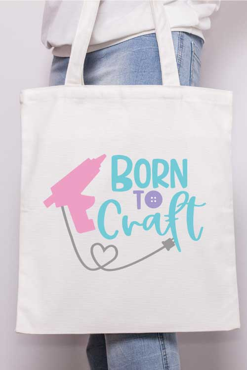 "Vertical - Someone holding a canvas tote with the ""born to craft"" svg design with glue gun applied in iron vinyl"