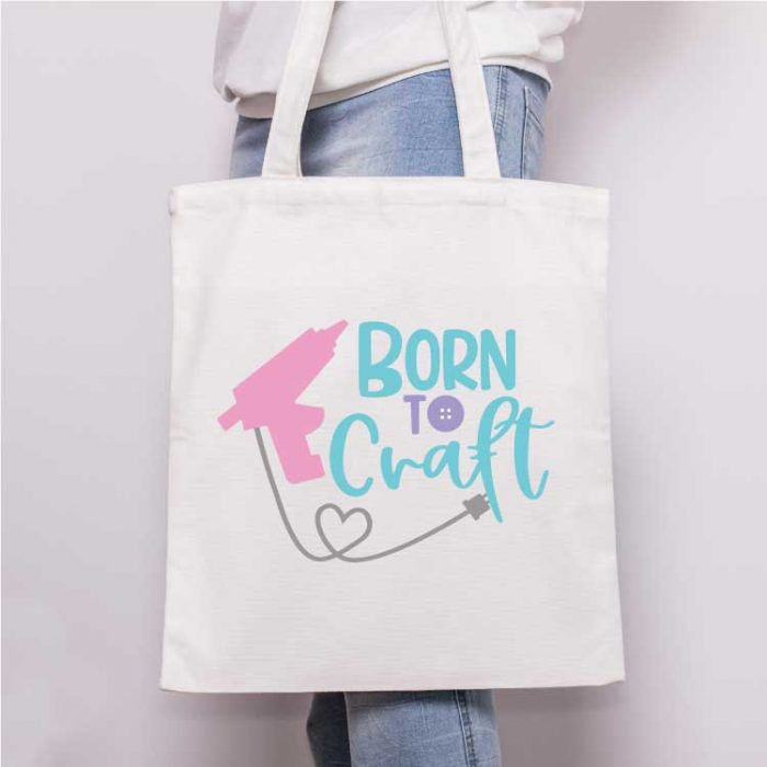 "Square - Close up of someone holding a canvas tote with the ""born to craft"" svg design with glue gun applied in iron vinyl"