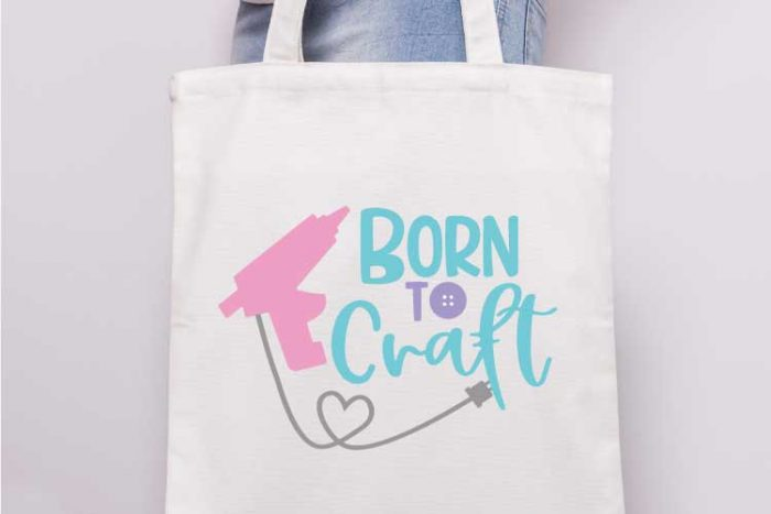 "Close up of someone holding a canvas tote with the ""born to craft"" svg design with glue gun applied in iron vinyl"