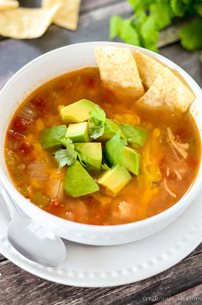 Chicken Tortilla soup with avocado and cilantro garnish with some tortilla strips on the side.