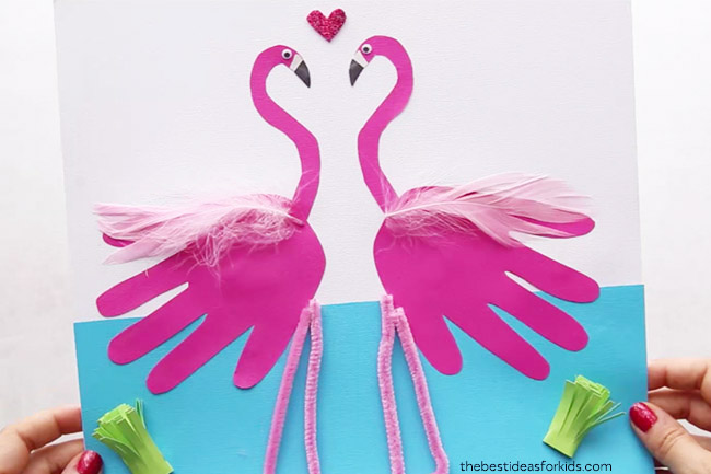 Pink handprint paper cutouts turned into flamingo crafts.