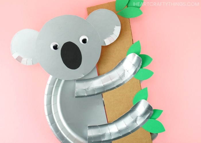Koala craft made from paper plates hanging onto a paper bamboo tree