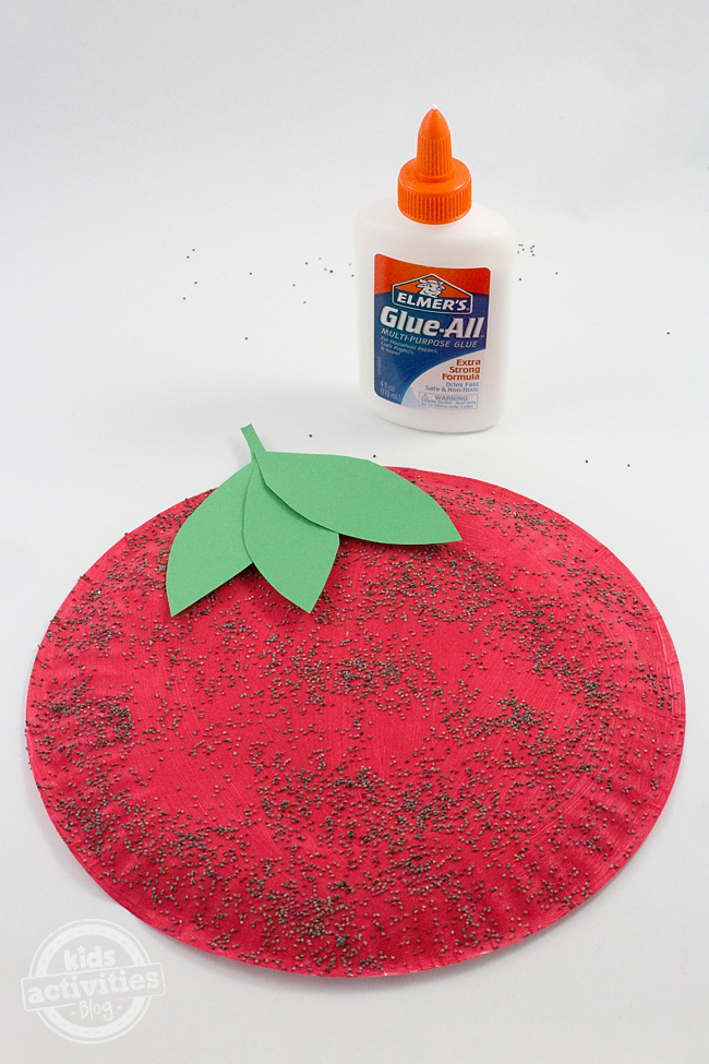Paper plate craft painted as a strawberry with poppyseed seeds.