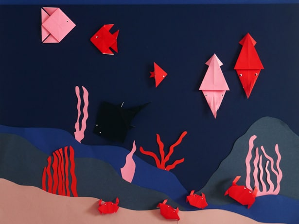 Origami sea creatures in a construction paper sea scene.