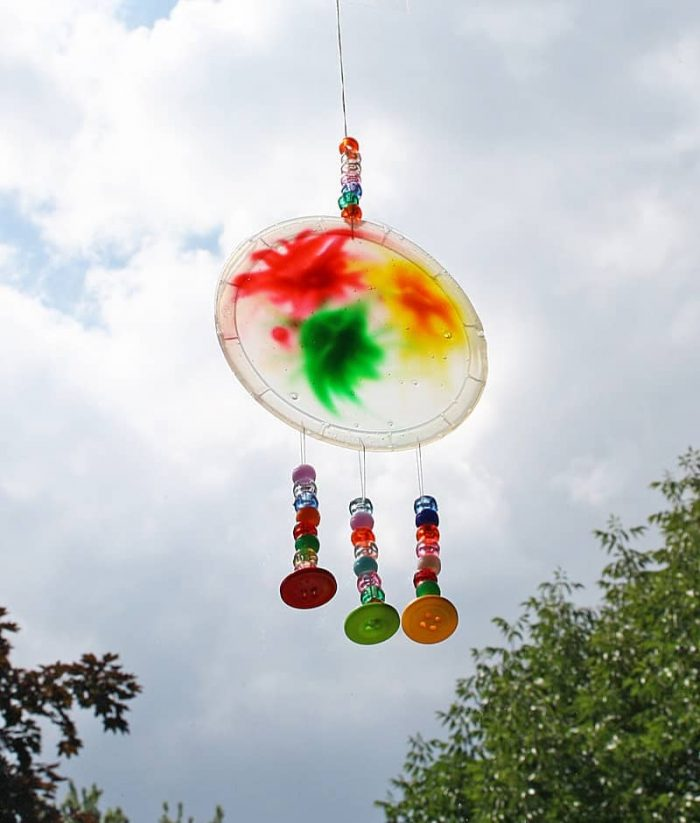 Tinted glue on plastic made into a sun catcher with added bead embellishments.