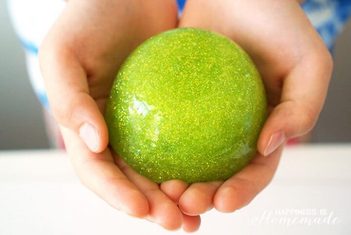 Hands holding a ball of green sparkly slime.