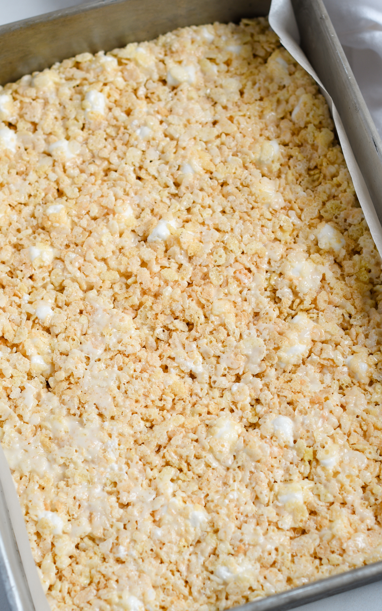 Overhead shot of rice krispie treats cooling in the pan