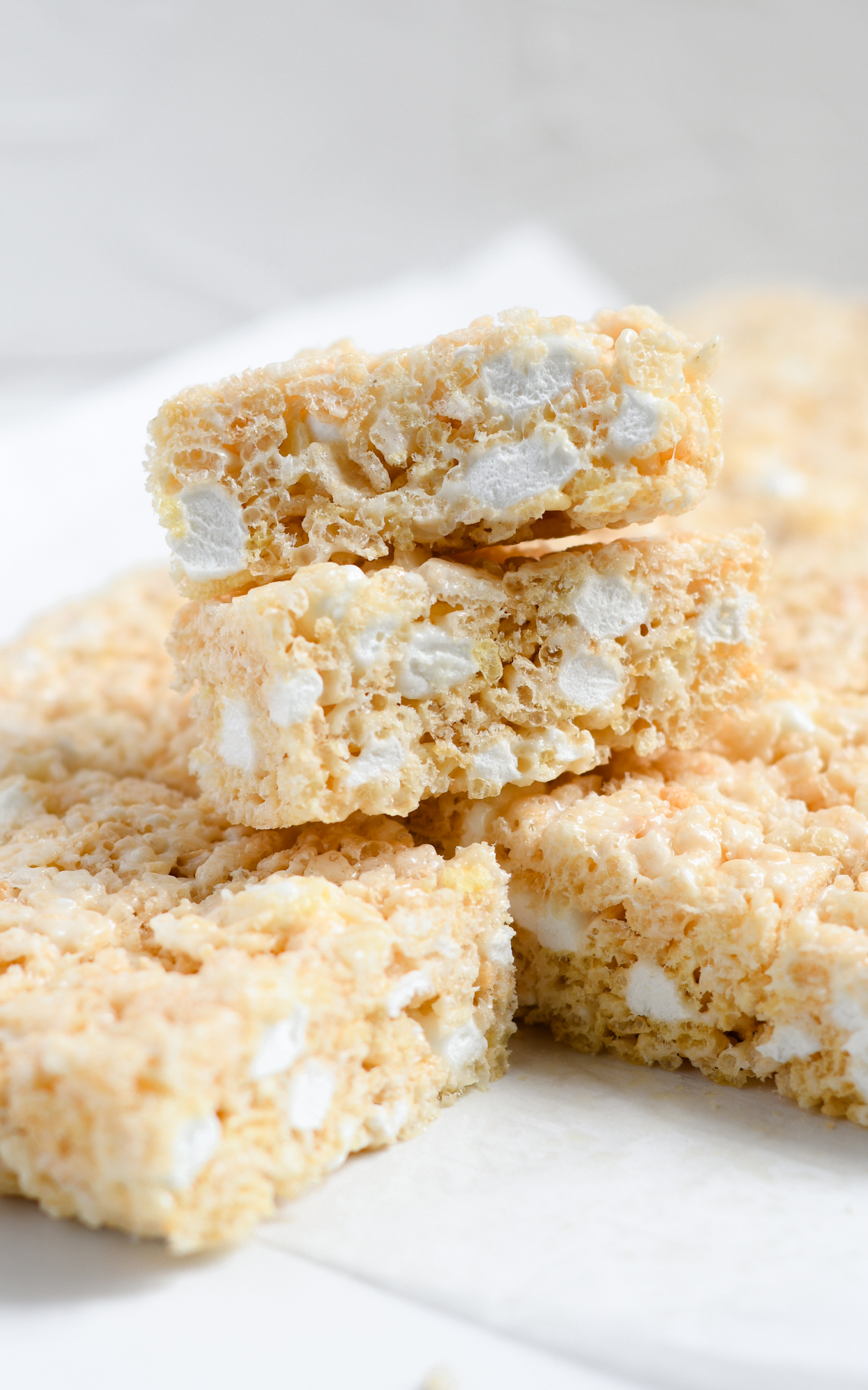 Close up of cut rice krispie treats stacked on a plate