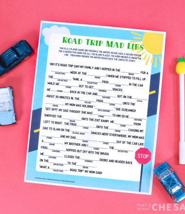 Coral background with Road Trip Mad Lib Printable and a pen and some matchbox cars Square Format