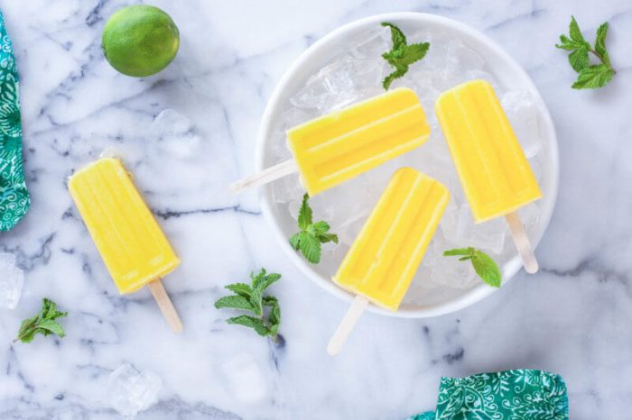 Mango Pineapple Popscicles laying on a bowl of ice