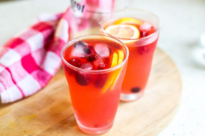 Finished product of berry lemonade garnished with lemons and berries.