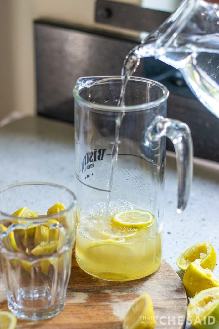 Pouring water in a pitcher filled with lemons and lemon juice.