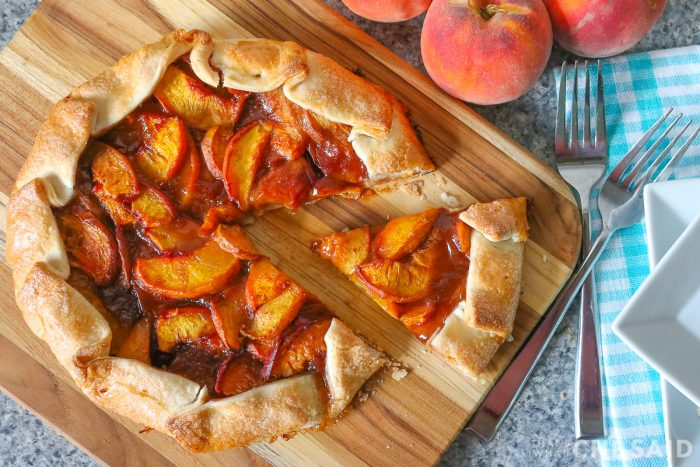 Peach Galette with slice removed on bamboo cutting board with forks and plates