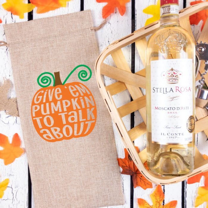 Burlap Wine Bottle Bag with Free Pumpkin SVG with iron on next to basket with some wine.  Fall leaves in background.