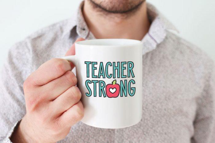 "Man holding white coffee mug with ""Teacher Strong"" design in adhesive vinyl - horizontal format"