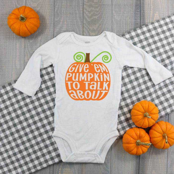 "White baby bodysuit with ""Give 'em pumpkin to talk about"" in iron on."