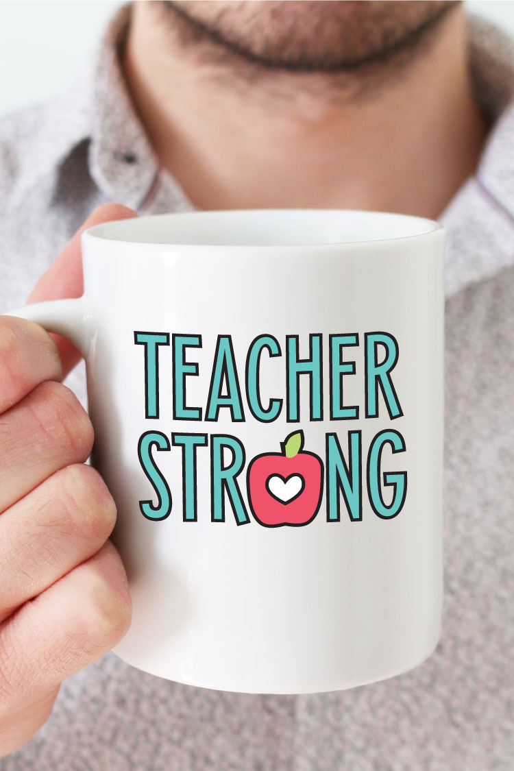 "Man holding white coffee mug with ""Teacher Strong"" design in adhesive vinyl - vertical format"