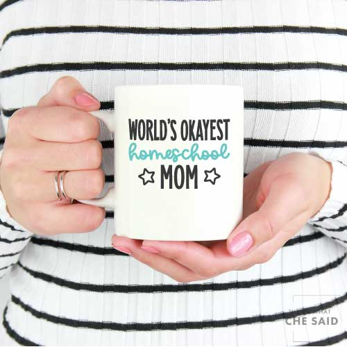"""Woman holding Coffee Mug with """"World's Okayest Homeschool Mom"""" applied with adhesive vinyl"""