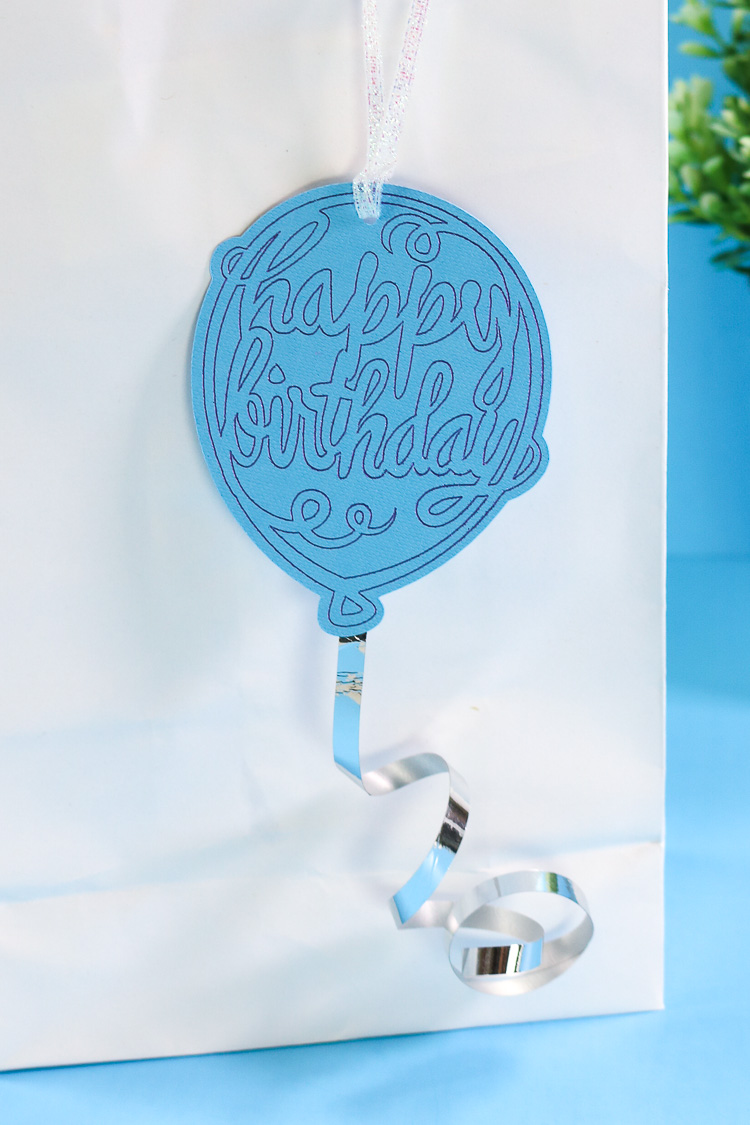Happy Birthday Balloon Gift tag with ribbon tail hanging from a white gift bag