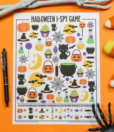 Orange background with Halloween I-spy printable and a pen and halloween decorations around it - vertical orientation