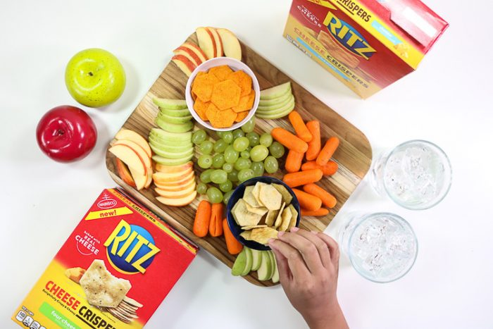 Child reaching for a Ritz Cheese Crisper on a board of snacks,fruits and veggies