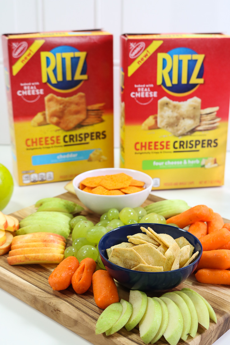 Both boxes of cheese cripsers next to board of snacks
